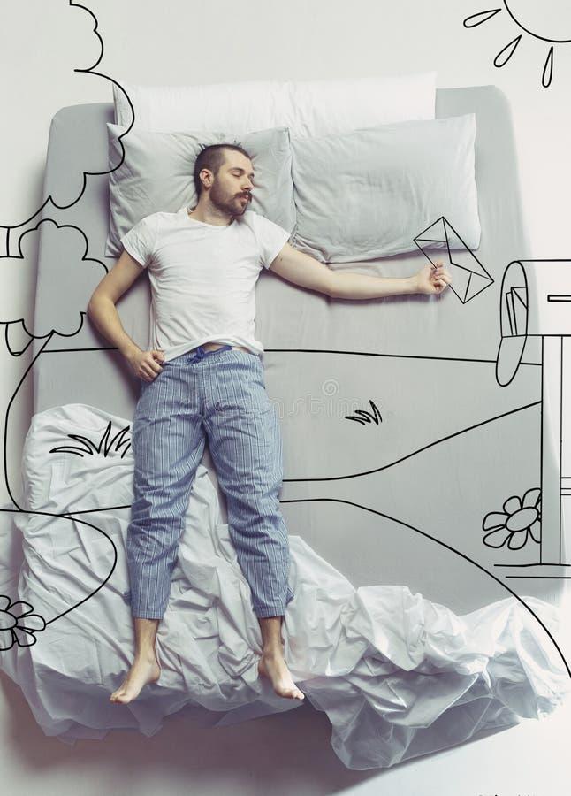 Foto de la visión superior del hombre joven que duerme en una cama blanca grande y sus sueños foto de archivo