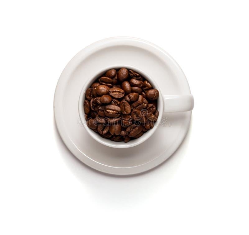 Foto de la visión superior de una taza de café llenada de los granos y del platillo de café aislados en el fondo blanco imagenes de archivo