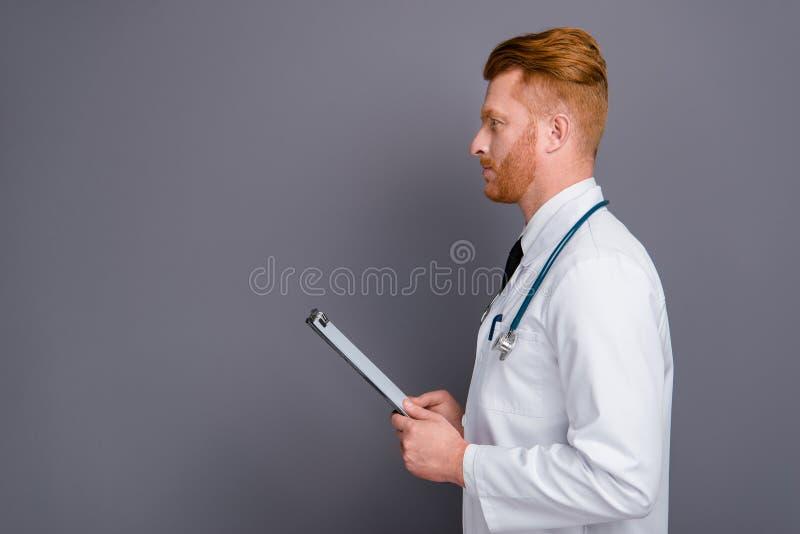 Foto de la vista lateral del perfil del doctor agradable de la calma aislado en gra oscuro imagenes de archivo