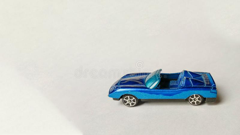 Foto de la vista lateral tirada del coche azul del juguete para los niños en el fondo blanco imagen de archivo libre de regalías