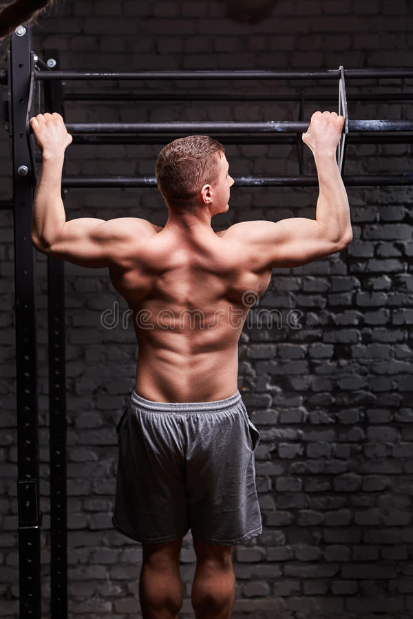 Foto de la vista posterior del varón muscular joven que hace ejercicios en barra horizontal contra la pared de ladrillo en el gim imágenes de archivo libres de regalías