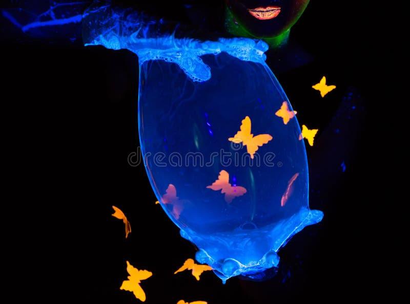 Foto de las manos de la mujer que llevan a cabo la burbuja luminosa foto de archivo