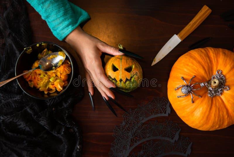 Foto de las manos del ` s del hombre con el enchufe de la calabaza, araña, cuchillo que se sienta en la tabla de madera imagenes de archivo