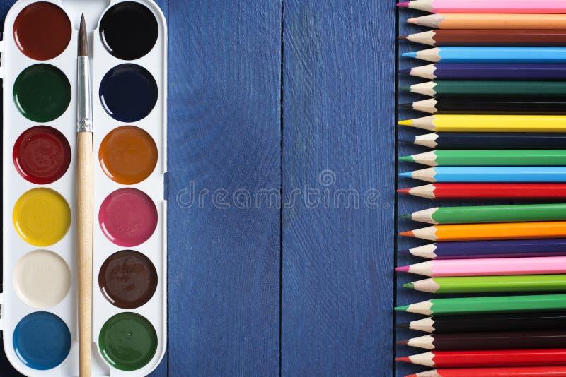 Foto de las pinturas de la acuarela con un cepillo a pintar y que miente delante de los lápices coloreados en el escritorio de la imagen de archivo