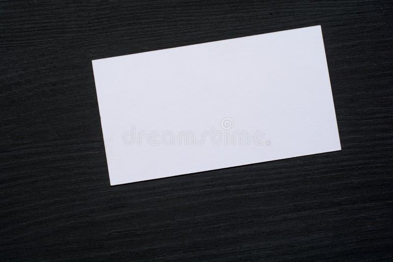Foto de las tarjetas de visita blancas en blanco en un fondo de madera oscuro Maqueta para la identidad de marcado en caliente fotos de archivo