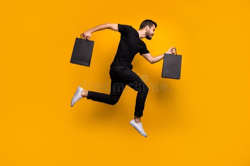 Foto de longa data de um cara bonito do milênio saltando em um shopping de alta competição comprando novas roupas segurando sacos imagens de stock royalty free