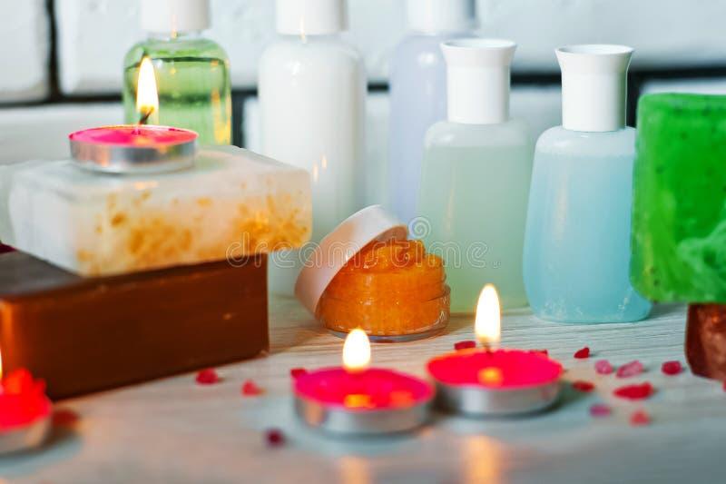 Foto de los cuartos de baño, tratamientos del balneario Botellas transparentes, lufa, pedazos de jabón, sales de baño, velas como fotos de archivo