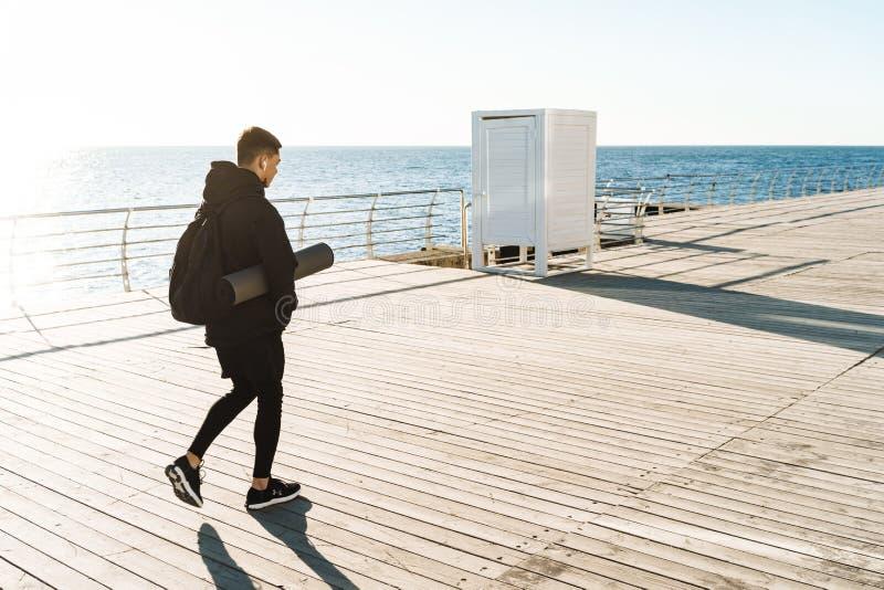 Foto de los earpods que llevan del deportista atlético que caminan por la playa después de entrenamiento de la mañana fotografía de archivo libre de regalías