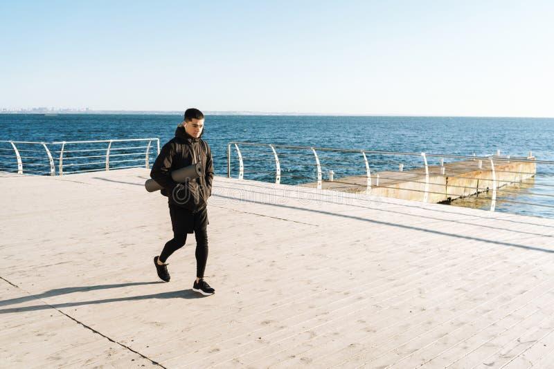 Foto de los earpods que llevan del deportista caucásico que caminan por la playa después de entrenamiento de la mañana fotografía de archivo