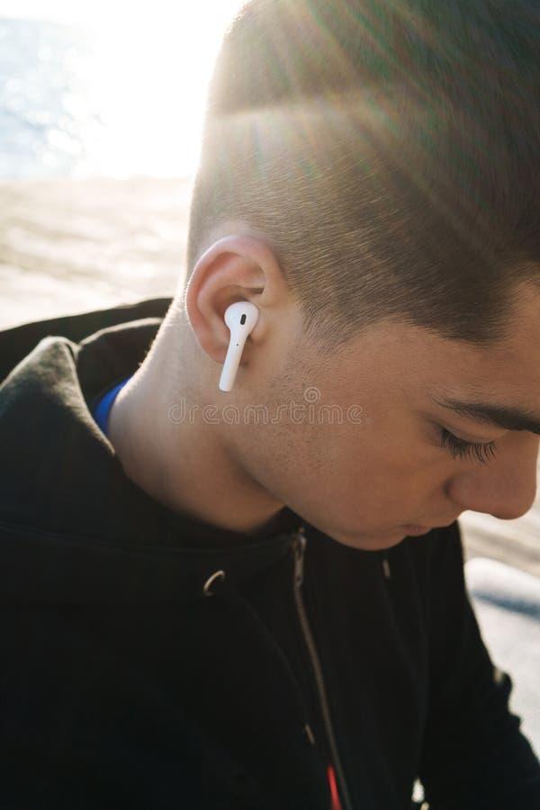 Foto de los earpods que llevan del deportista joven que caminan por la playa por la mañana mientras que hace deportes imagen de archivo