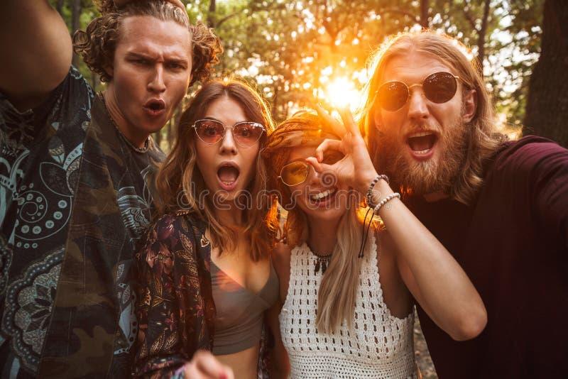 Foto de los hombres y de las mujeres alegres de los hippies, sonriendo y tomando a uno mismo imagen de archivo