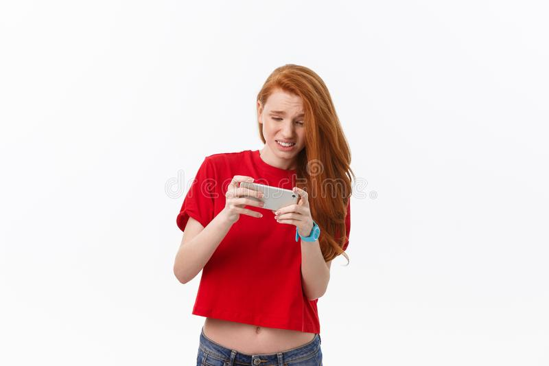 Foto de los juegos caucásicos jovenes emocionales del juego de la mujer por el teléfono Mirada a un lado imagen de archivo libre de regalías