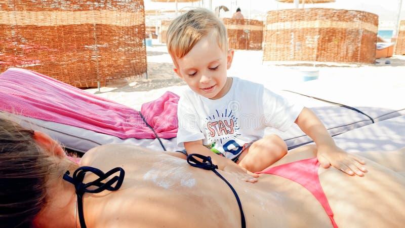 Foto de los 3 a?os lindos del ni?o peque?o que hace masaje a la madre joven que se relaja en la cama del sol en la playa del mar imágenes de archivo libres de regalías