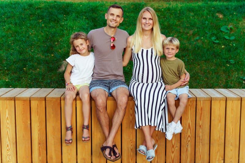Foto de los padres y de dos niños que se sientan en la cerca de madera fotografía de archivo