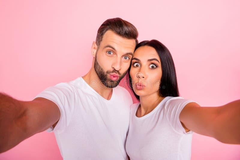 Foto de los pares cómicos divertidos encantadores agradables que se besan a través de cámara mientras que está aislado con el fon imagen de archivo libre de regalías