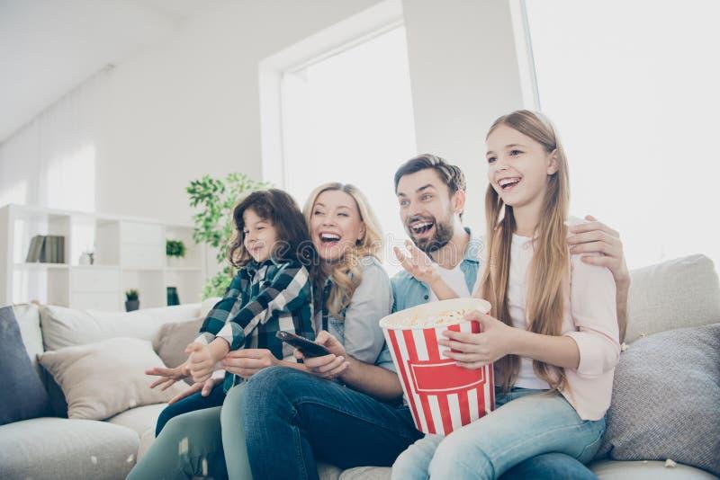 A foto de membros grandes da família quatro passa o tempo de lazer olhando o programa televisivo sentar o sofá come a pipoca salg imagem de stock royalty free