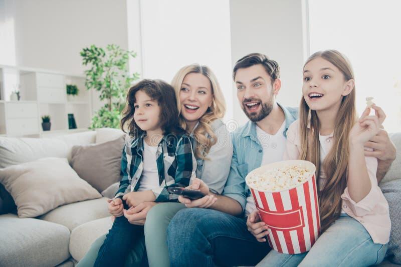 A foto de membros grandes da família quatro passa o tempo de lazer olhando o programa televisivo sentar o sofá come a pipoca salg fotos de stock