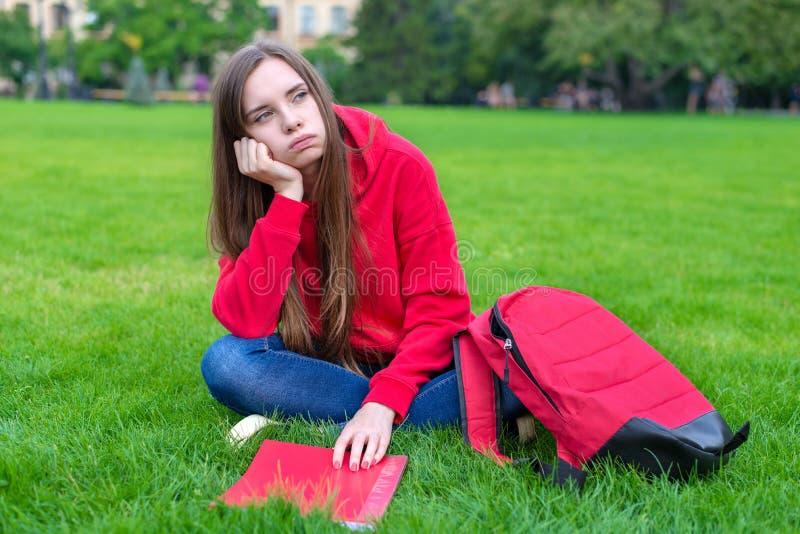 A foto de menina adolescente triste passiva deprimida que senta-se no gramado da grama verde não é disposta fazer em casa a taref imagens de stock