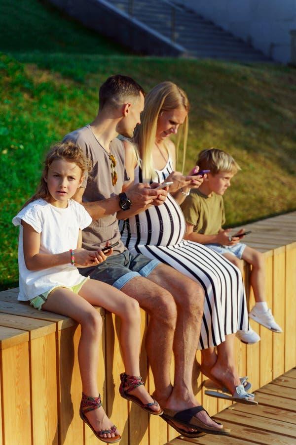 Foto de padres con la hija y el hijo que se sientan en la cerca de madera con los teléfonos en manos imágenes de archivo libres de regalías