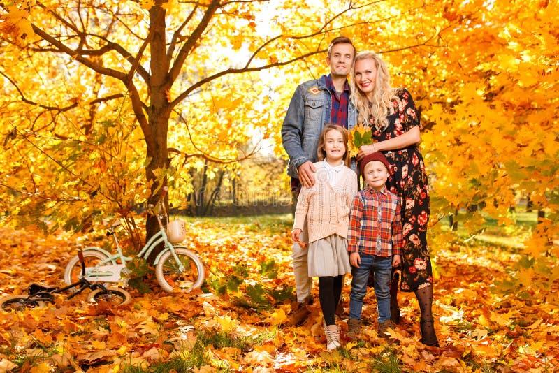 Foto de pais e de crianças novos na caminhada no parque do outono fotos de stock