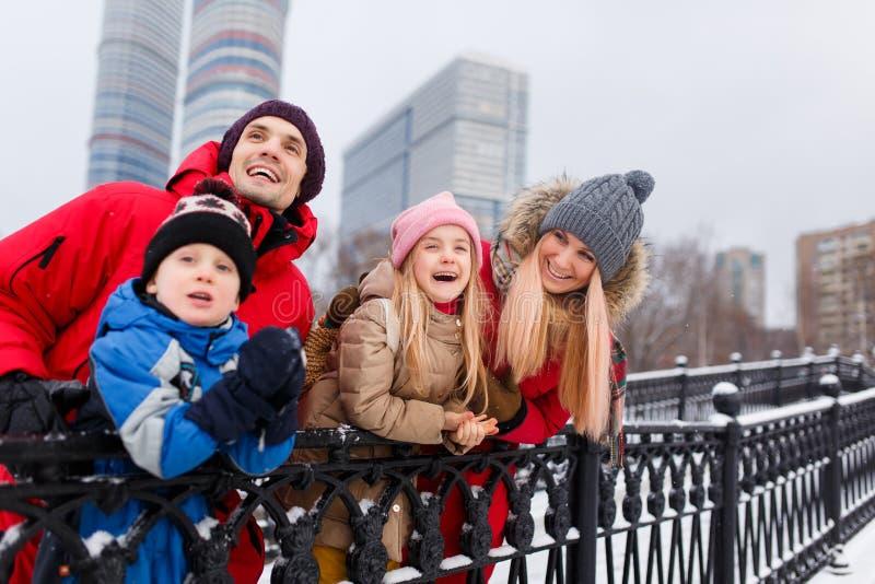 A foto de pais felizes com filha e o filho no inverno andam foto de stock