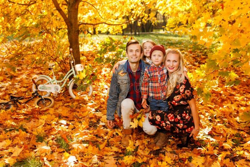 Foto de pais felizes e das crianças que sentam-se no parque do outono imagens de stock royalty free