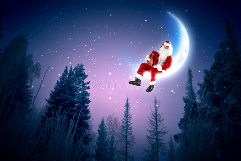 Foto de Papai Noel que senta-se na lua foto de stock royalty free
