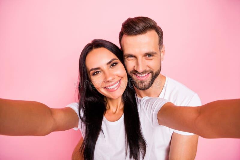 Foto de pares agradables con el hombre que abraza a su novia querida de la parte posterior mientras que está aislado con el fondo imagenes de archivo