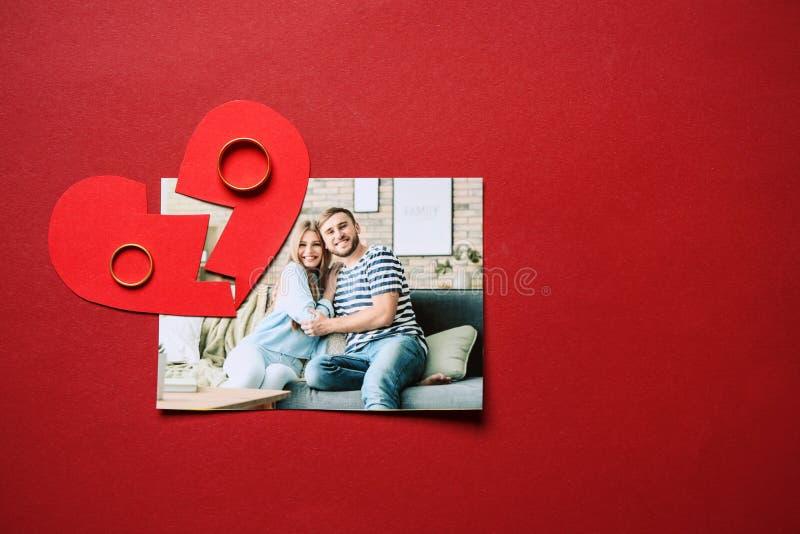 Foto de pares felices con los anillos y el corazón quebrado en fondo del color Concepto de divorcio foto de archivo