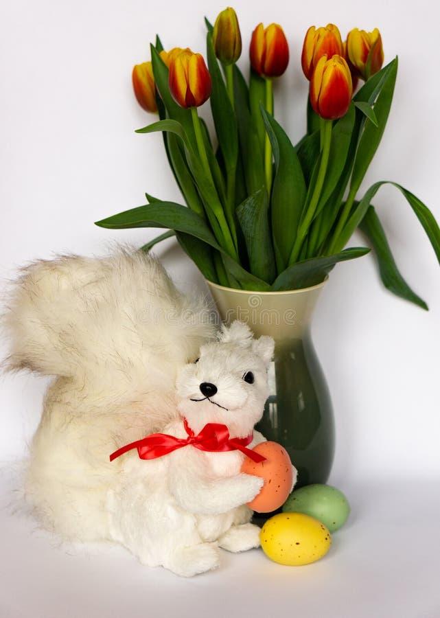 Foto de Pascua con el apoyo de la ardilla, los huevos de Pascua, y el florero blancos de tulipanes foto de archivo
