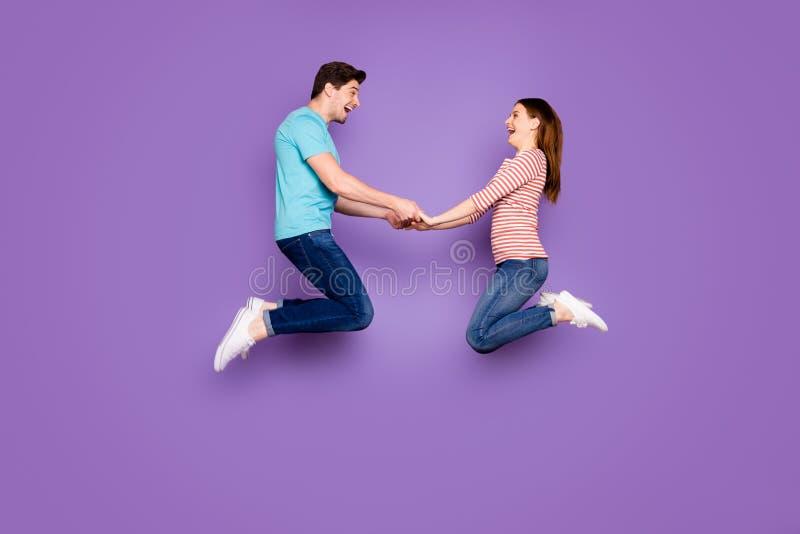 Foto de perfil completo de dos personas asombradas, una mujer saltando con las manos llenas de alegría de divertirse usando un az fotografía de archivo libre de regalías