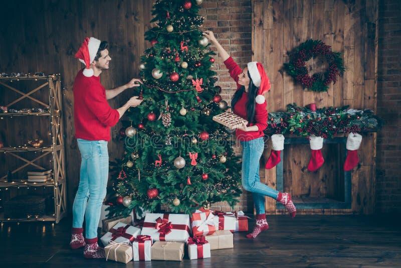 Foto de perfil de tamaño completo de dos cónyuges románticos con gente sosteniendo baubles decoran árbol de Navidad para lleva imagen de archivo libre de regalías