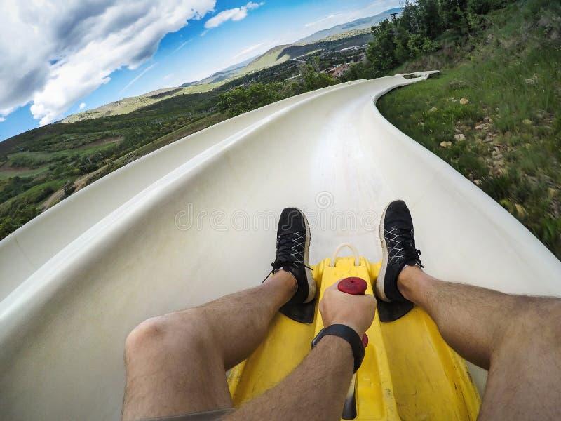 Foto de Point of View de un hombre que monta abajo de una diapositiva alpina en declive del práctico de costa en vacaciones de la foto de archivo