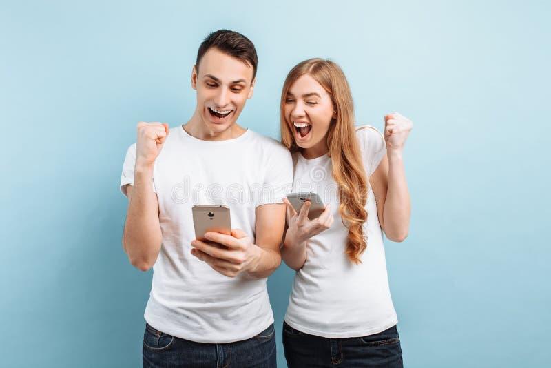 Foto de povos entusiasmados, homens e mulheres, felizmente mostrando um gesto da vitória e do sucesso, guardando smartphones em s foto de stock royalty free