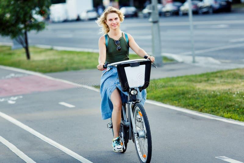 Foto de rubio joven en bici larga del montar a caballo de la falda del dril de algodón en el camino en ciudad foto de archivo