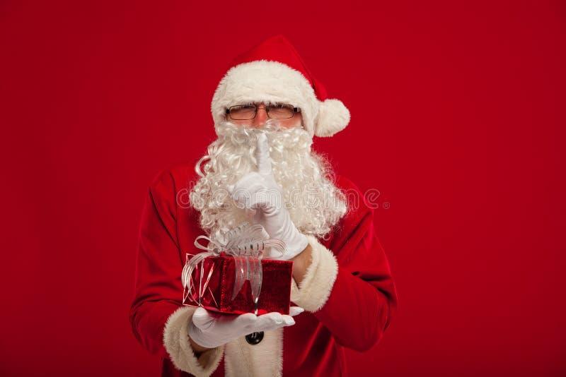 Foto de Santa Claus amável que dá o presente do xmas e que olha a came imagens de stock