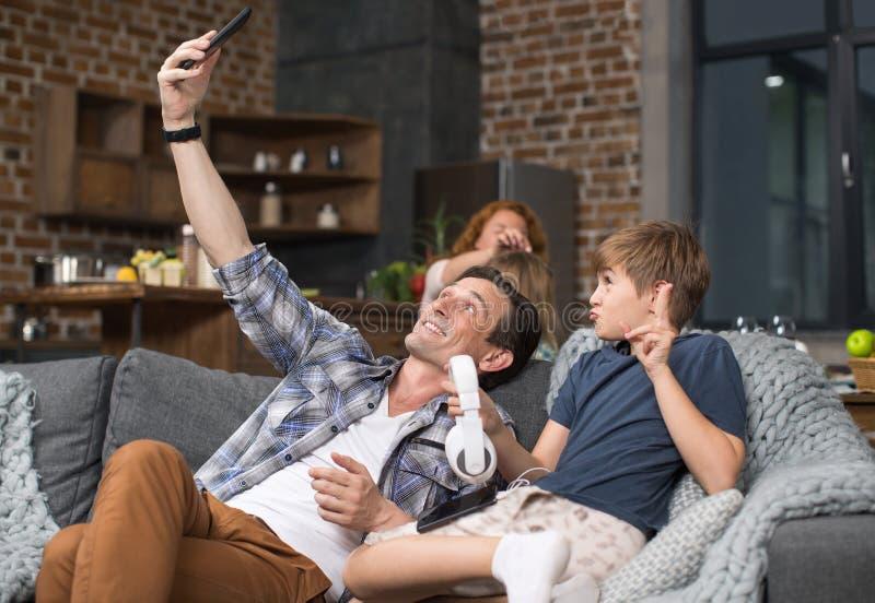 Foto de And Son Take Selfie del padre en el teléfono elegante de la célula que se sienta en el sofá en sala de estar imágenes de archivo libres de regalías