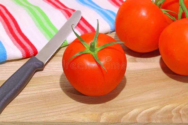 Foto de tomates vermelhos no fundo de madeira com faca especial fotografia de stock