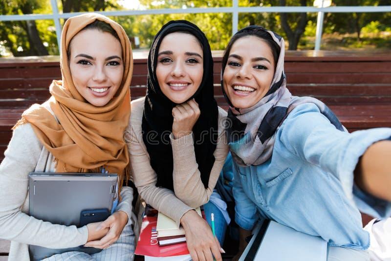 Foto de tres estudiantes musulmanes que llevan los headscarfs que se sientan en banco en parque fotos de archivo libres de regalías