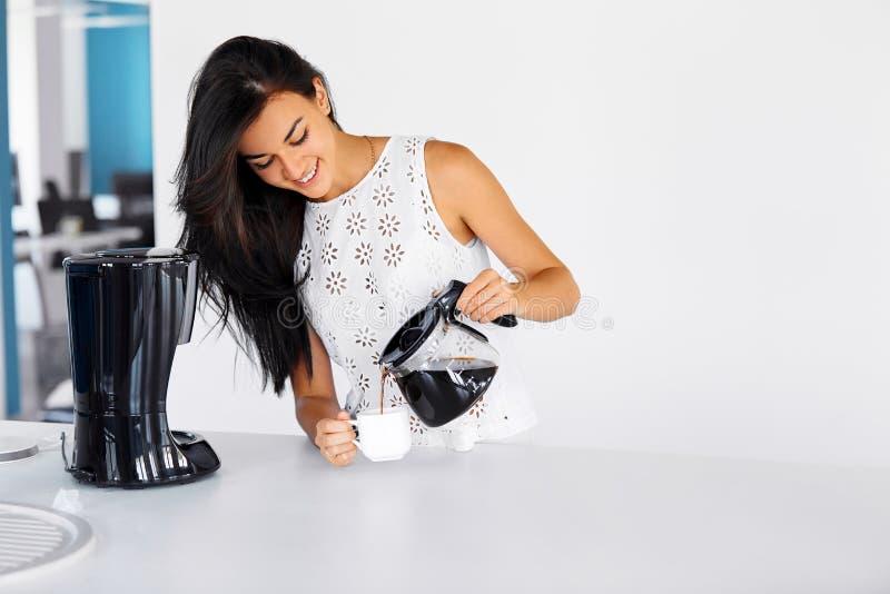 Foto de um café de derramamento da mulher de um potenciômetro de vidro fotos de stock
