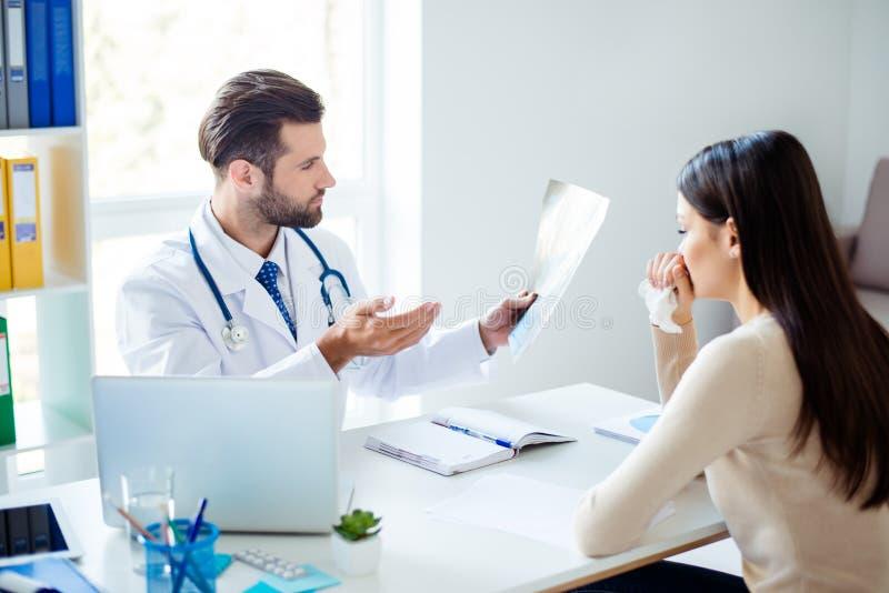 Foto de um doutor que guarda resultados do diagnóstico e que informa os imagem de stock