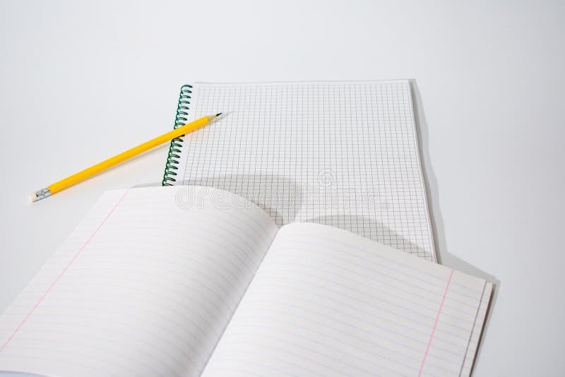 Foto de um fragmento de dois cadernos e de um lápis em um fundo branco com espaço para o texto imagem de stock