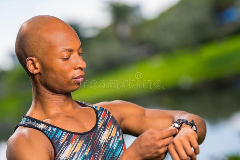 Foto de um modelo da aptidão que ajusta seu relógio esperto fotos de stock royalty free