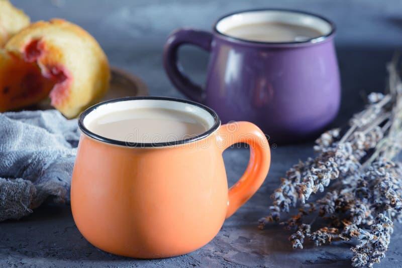 Foto de uma bebida quente no estilo rústico Duas canecas pequenas com um café Ao lado da alfazema em um queque imagem de stock royalty free