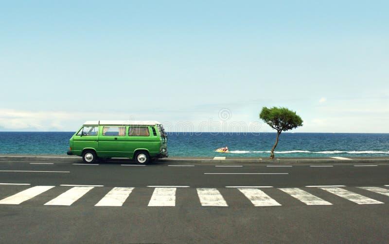 Foto de uma camionete verde na estrada e no mar imagem de stock