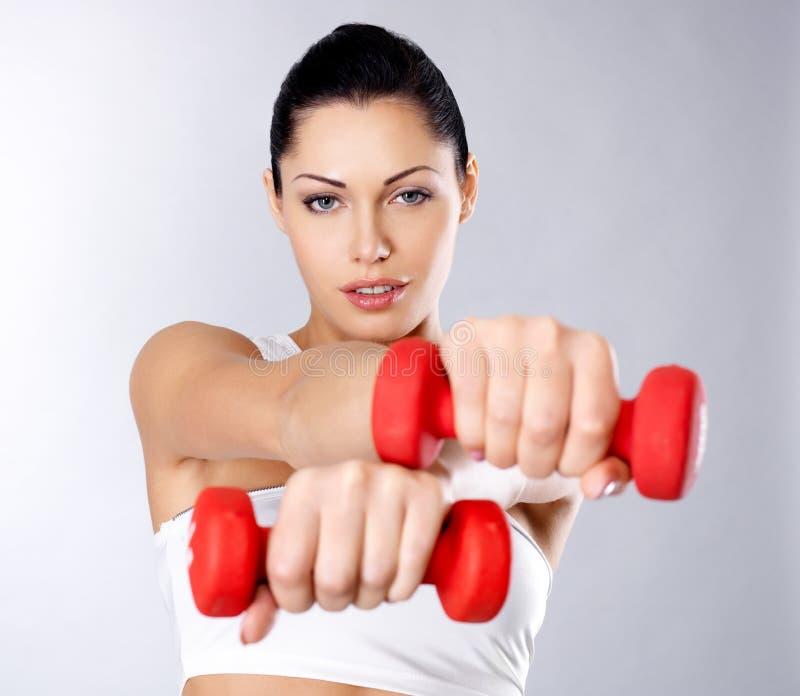 Foto de uma jovem mulher saudável do treinamento com dumbbells imagem de stock royalty free