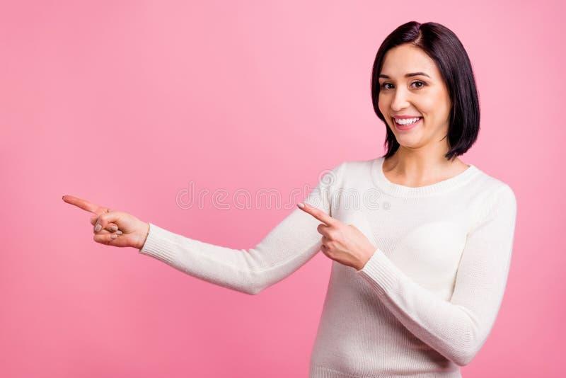 Foto de uma mulher de negócios engraçada indicando dedos ao espaço vazio em preços de venda vestem pullover branco isolado rosa b fotos de stock royalty free