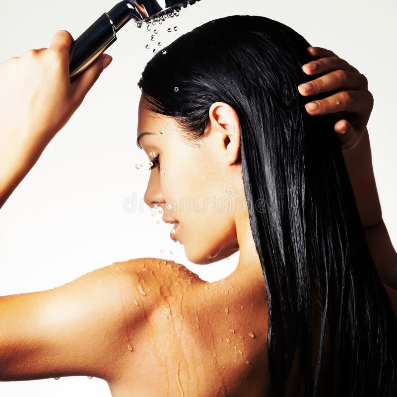 Foto de uma mulher no chuveiro que lava o cabelo longo foto de stock