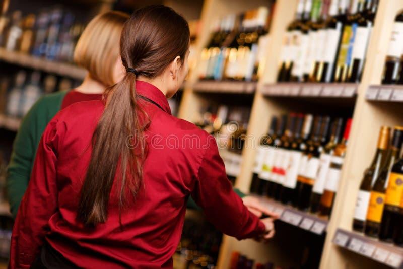 Foto de uma parte traseira de duas jovens mulheres na loja de bebidas, fotografia de stock royalty free
