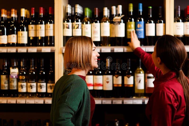 Foto de uma parte traseira de duas jovens mulheres na loja de vinhos imagens de stock